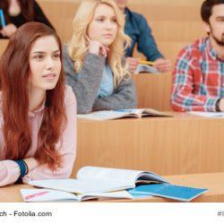 Eine Studentin folgt interessiert einer Vorlesung.