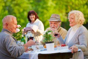 Senioren beim Geburtstag feiern mit Kuchen und Wein im Garten