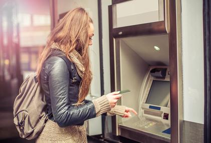 Junge Frau hebt Geld vom Geldautomaten ab