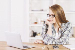 Eine junge Frau am Laptop im häuslichen Arbeitszimmer