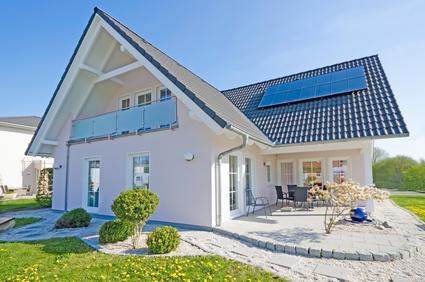 Weißes Einfamilienhaus mit Photovoltaik-Anlage auf dem Dach.