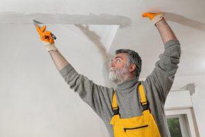 Ein Handwerker spachtelt und repariert eine Wand und die Decke