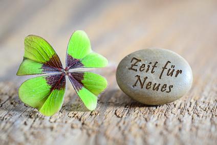 """Ein vierblättriges Kleeblatt und ein Stein mit der Inschrift """"Zeit für Neues"""""""